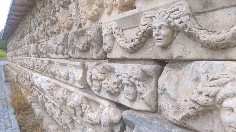 Güney Agora'nın kuzey cephesindeki Tirius Portikosuna ait olan baş kabartmaları. Kazıevinin duvarında sergileniyor.